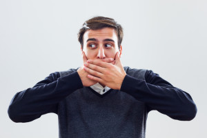 Man Covering Mouth to Hide Severe Teeth Stains